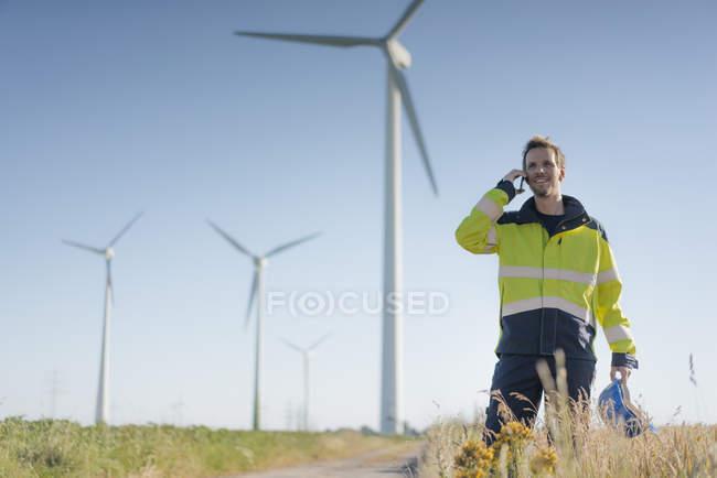 Ingeniero sonriente parado en un campo en un parque eólico hablando por teléfono celular - foto de stock