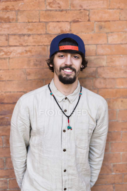 Portrait of relaxed young man wearing basecap and necklace — Stock Photo