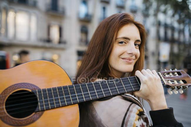 Rothaarige Frau mit Gitarre in der Stadt — Stockfoto