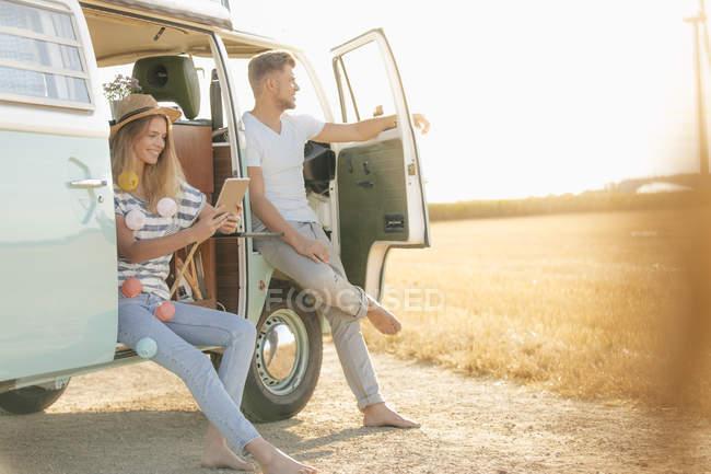Молодая пара отдыхает в кемпере фургона в сельской местности, женщина просматривает цифровые планшеты — стоковое фото