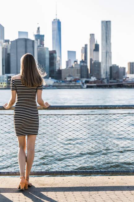 USA, New York, Brooklyn, vista posteriore della donna in piedi di fronte all'East River — Foto stock