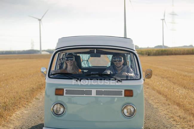 Улыбающаяся пара в очках VR за рулем фургона в сельской местности — стоковое фото