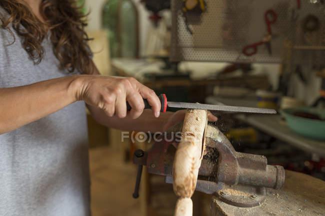 Handwerkerin feilt in ihrer Werkstatt an einem Stück Holz — Stockfoto