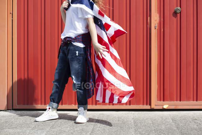 Chica de pie en la pared roja con bandera estadounidense - foto de stock