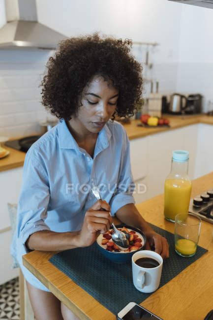 Женщина завтракает в своей кухне, едят фрукты — стоковое фото