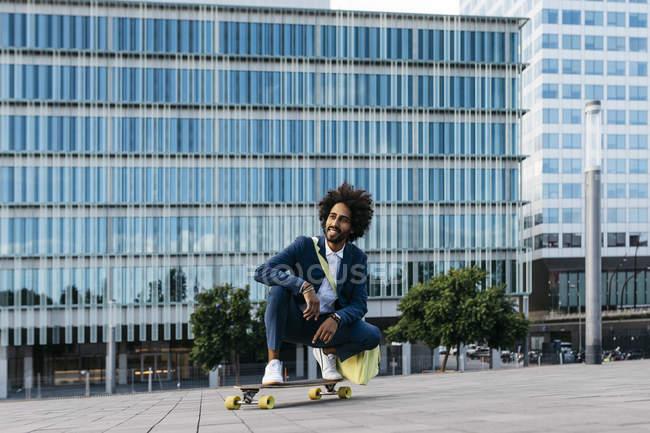España, Barcelona, joven empresario agachado en monopatín en la ciudad - foto de stock