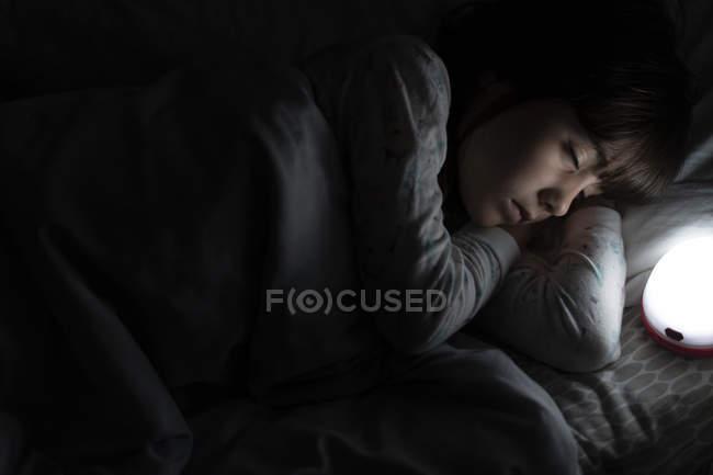 Ragazza che dorme a letto di notte con luce notturna — Foto stock