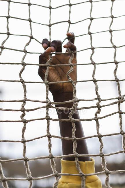 Imagem recortada de afro-americano segurando a rede de voleibol — Fotografia de Stock