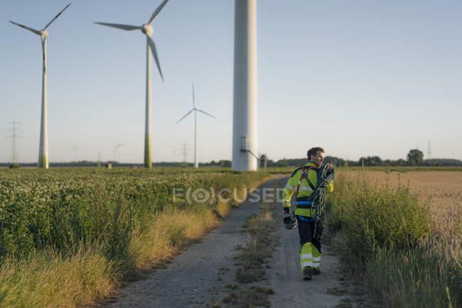 Tecnico che cammina sul campo in un parco eolico con attrezzatura da arrampicata — Foto stock