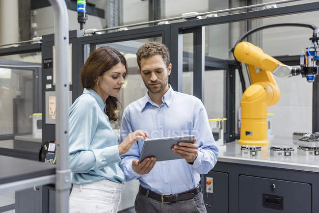 Colleagues in high tech company controlling industrial robots, using digital tablet - foto de stock