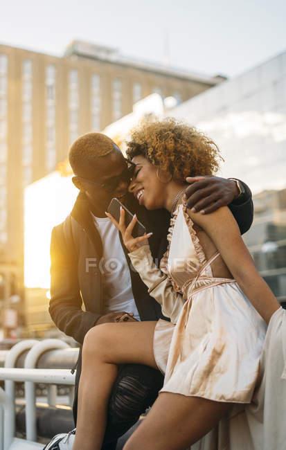 Glückliches Paar mit Handy in der Stadt bei Sonnenuntergang — Stockfoto