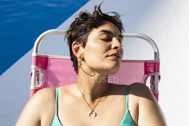 Retrato da mulher nova que relaxa no espreguiçadeira do sol na piscina — Fotografia de Stock