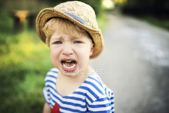 Portrait of screaming toddler wearing straw hat — Stock Photo