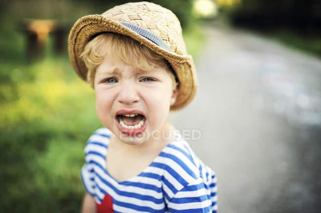 Портрет кричащего малыша в соломенной шляпе — стоковое фото