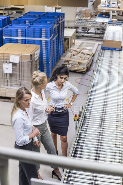 Three women discussing at conveyor belt in factory — Stock Photo