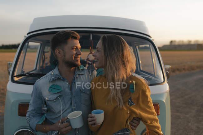 Щаслива молода пара на кемпер Ван в сільській місцевості на заході сонця — стокове фото