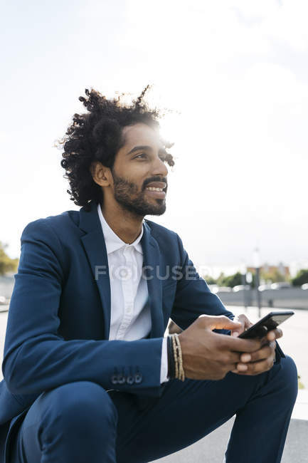 Smiling young businessman sitting outdoors and holding cell phone — Stock Photo