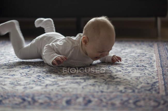 Crying baby girl lying on carpet, kicking legs — Stock Photo
