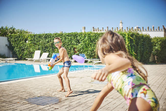 Girl and boy having a water fight with water gun and water bombs at the poolside — Stock Photo