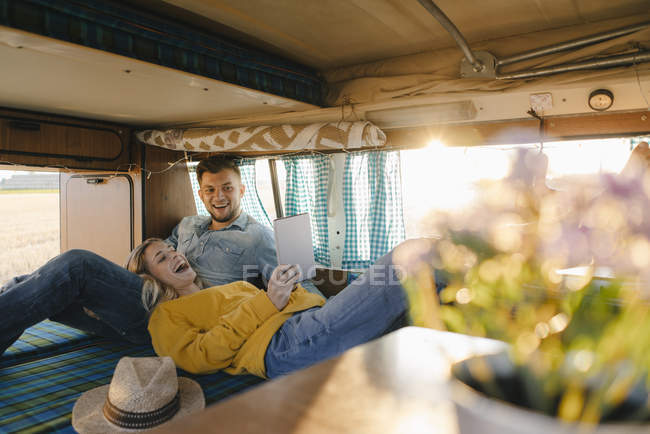 Happy young couple looking at tablet inside camper van — Stock Photo