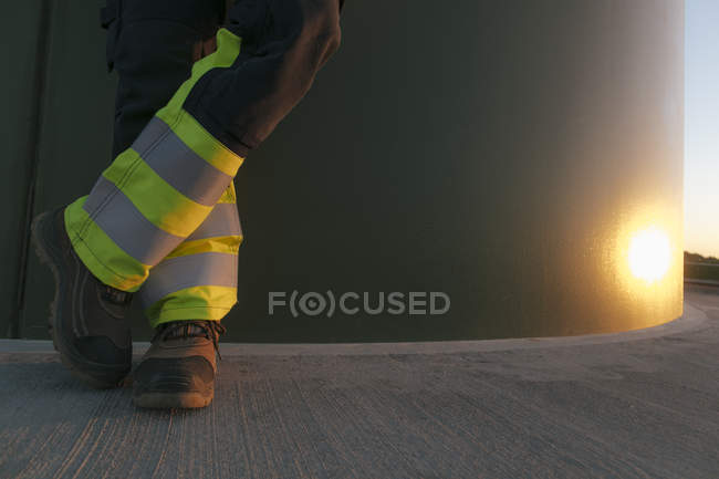 Cropped image of engineer standing at a wind turbine tower — Stock Photo