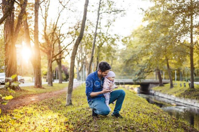Vater auf Kastaniensuche im Park, kleine Tochter auf dem Schoß — Stockfoto