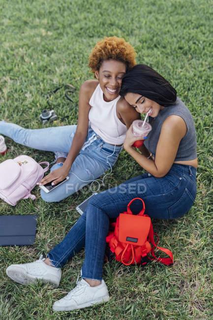Дві щасливі друзі жінки розслабляючий в парку — стокове фото