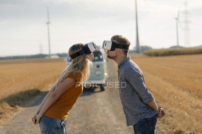 Молодая пара в очках VR целуется в фургоне в сельской местности — стоковое фото