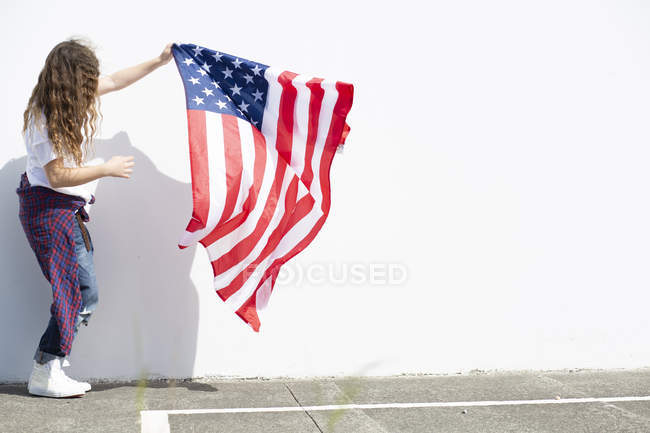 Girl holding American flag at white wall — Stock Photo