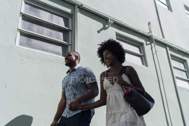 Smiling young couple walking along building — Stock Photo