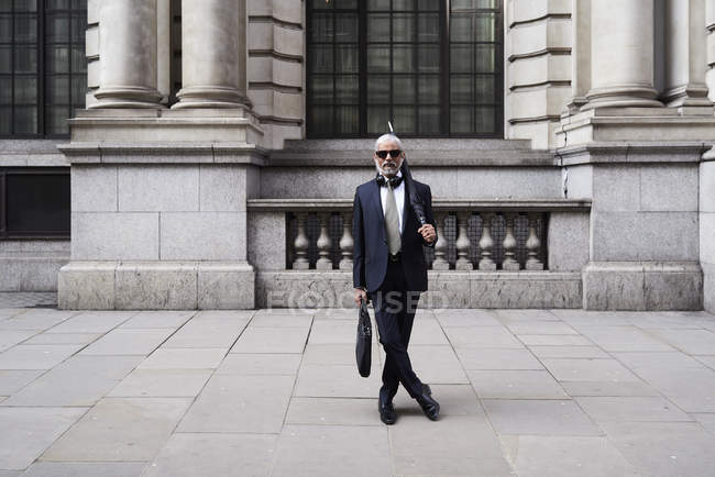 UK, London, portrait of stylish businessman with sunglasses and umbrella wearing suit and tie — Stock Photo