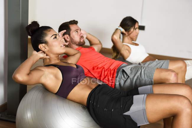 Jóvenes haciendo abdominales en una pelota de gimnasia - foto de stock