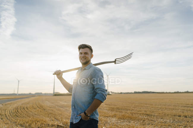 Portrait of smiling young man holding pitchfork standing on stubble field — Stock Photo