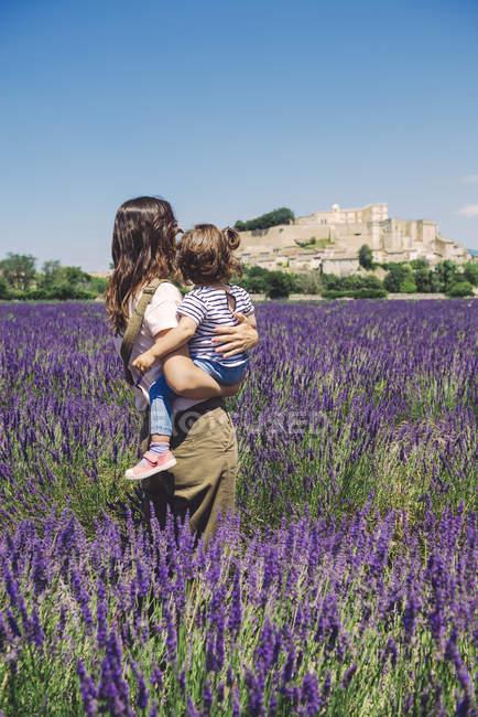 Франция, Гриньян, вид сзади на мать и маленькую дочь, стоящие вместе в лавандовом поле и смотрящие на деревню — стоковое фото