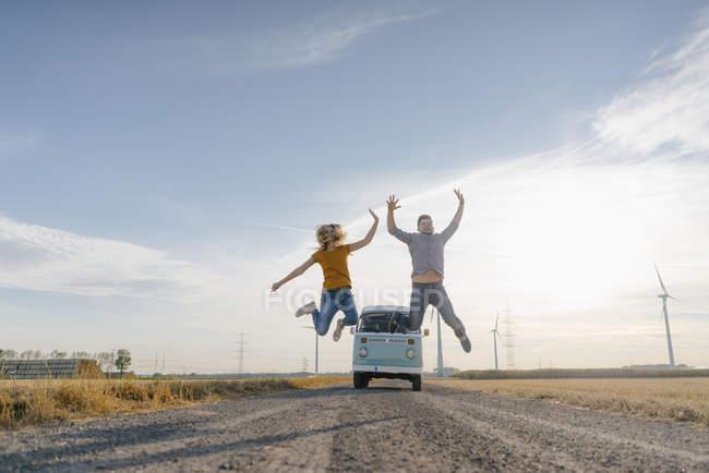 Couple exubérant sautant sur la piste de terre au camping-car dans le paysage rural — Photo de stock