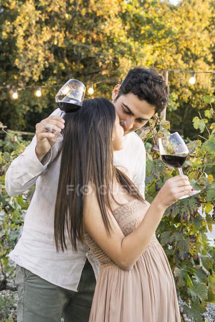 Italien, Toskana, Siena, liebevolles junges Paar mit Rotweingläsern im Weinberg — Stockfoto