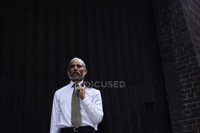 Портрет старшего бизнесмена с седыми волосами в белой рубашке и галстуке, стоя на темном фоне — стоковое фото