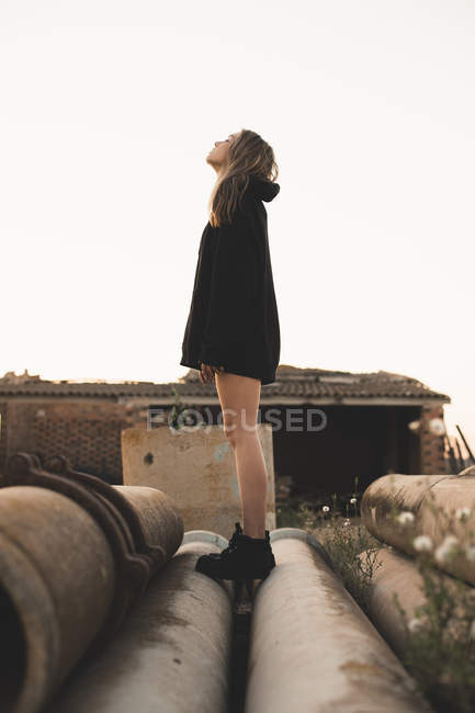 Blonde woman standing on tubes, looking up — Stock Photo