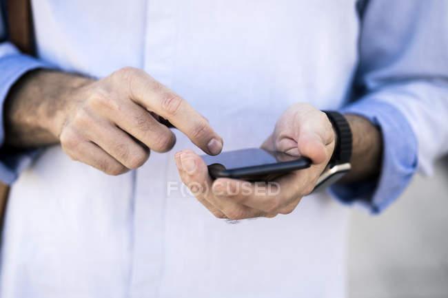 Imagen recortada de hombre de negocios utilizando el teléfono celular - foto de stock
