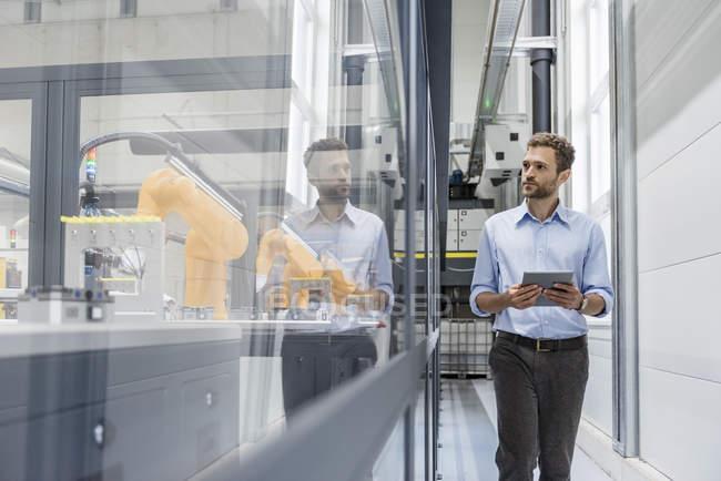 Homem de negócios que verific robôs com a tabuleta digital na companhia alta tecnologia — Fotografia de Stock