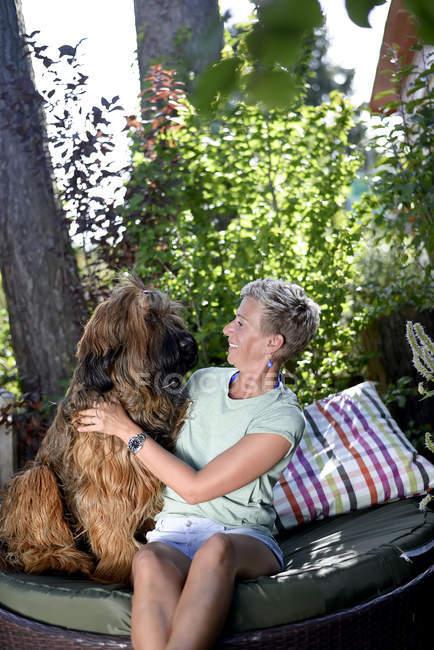 Усміхнена жінка з собакою в саду. — стокове фото