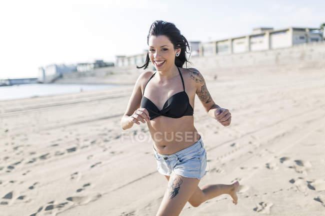 Portrait de jeune femme souriante avec des tatouages courant sur la plage — Photo de stock