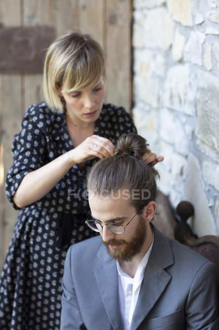 Женщина делает волосы молодого человека в сером костюме — стоковое фото