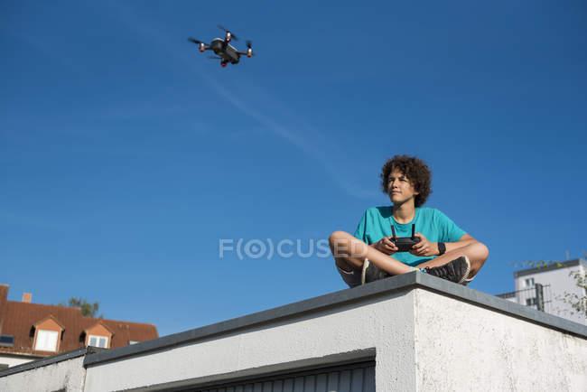 Ragazzo che naviga su un drone volante, seduto sul tetto del garage — Foto stock