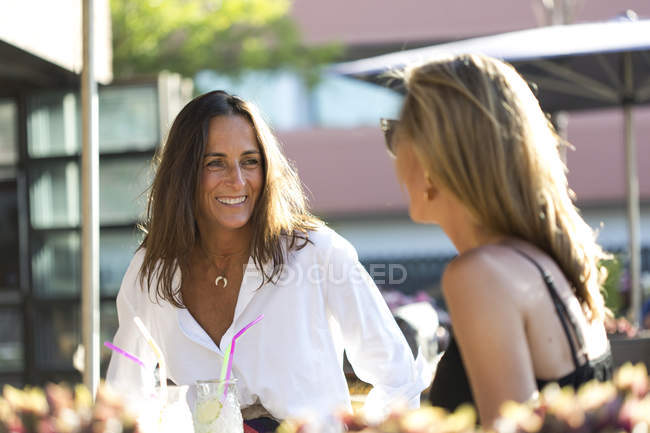 Happy girlfriends sitting outdoors with cocktail glasses — Stock Photo