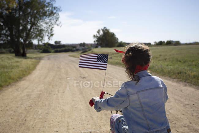 Ragazza con bandiera americana in bicicletta sul sentiero in paesaggio remoto — Foto stock