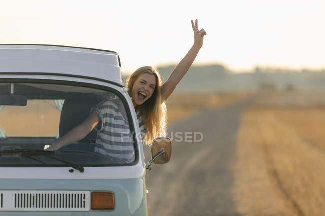 Excited young woman making victory hand sign out of camper van window in rural landscape — Stock Photo