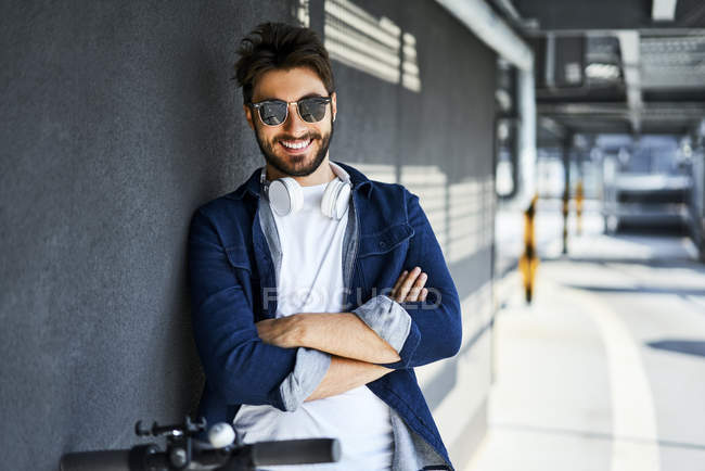 Portrait of smiling man wearing sunglasses and headphones — Stock Photo