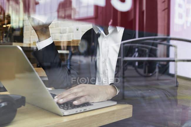 Homme d'affaires senior derrière la vitre dans un café travaillant sur ordinateur portable — Photo de stock