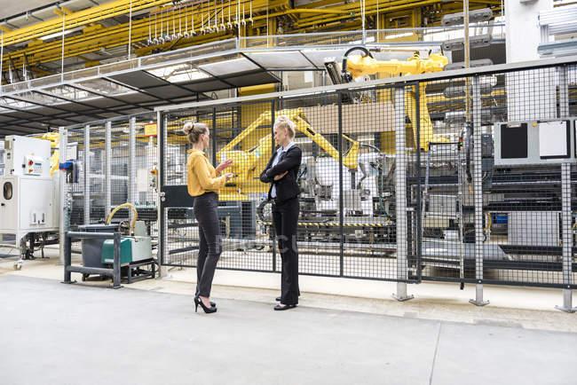 Two women talking in factory shop floor with industrial robot — Stock Photo
